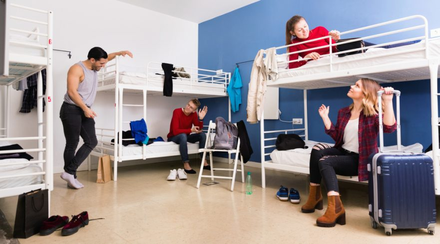 Young women and men staying at a hostel room