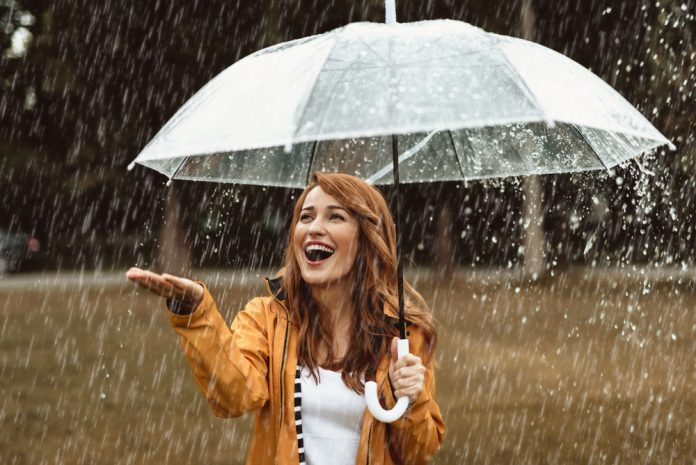 A happy young woman holding an umbrella and enjoying rain