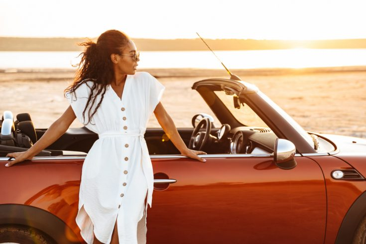 A black African woman in front of a beach leaning on her car