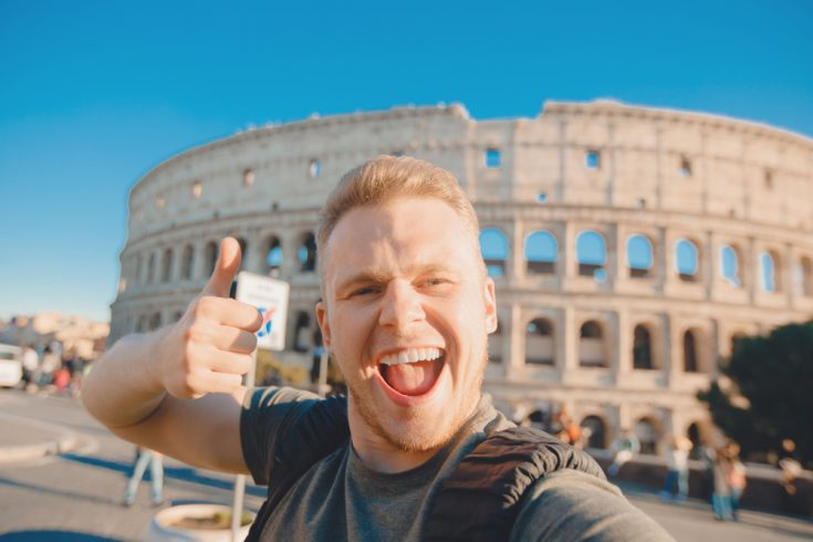 A happy man on a vacation taking a picture in front of Colosseum in Rome, Italy