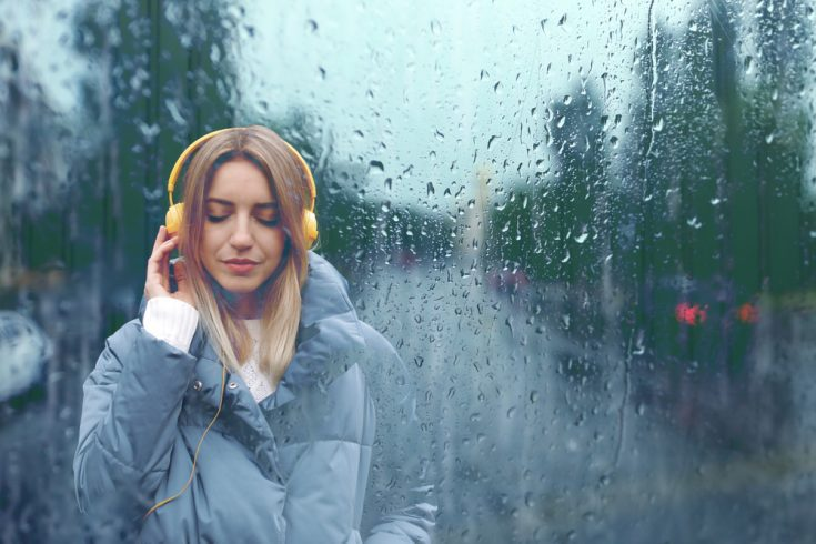 A young woman listening walking while listening to music on a rainy day