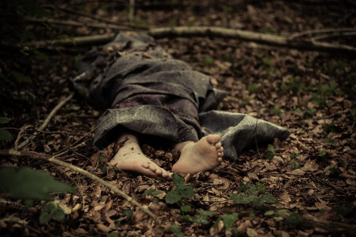 A dead body of a young boy abandoned in a forest