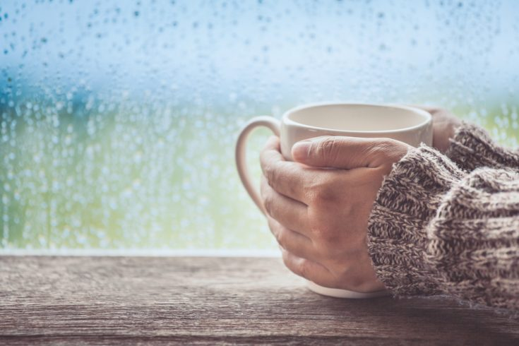 A girl drinking coffee or tea on a rainy day