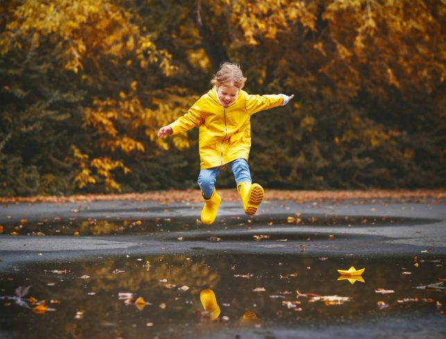 A happy child playing in the puddle of rainwater