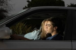 Teenage boy and girl (14-18) in car, girl kissing boy's cheek, night