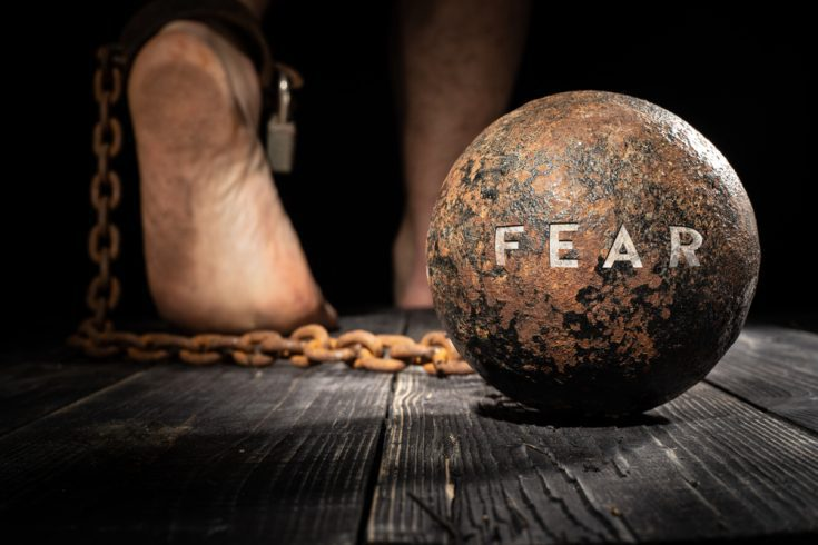 A person's feet tied to a ball of fear