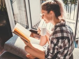 Woman drinking coffee while reading a book