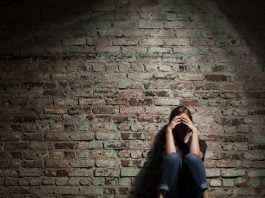 A stressed teenager sitting against a wall