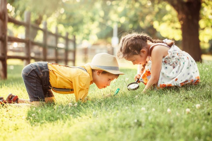 A young boy and a girl curious about something on grass