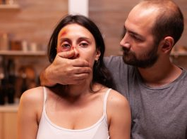An aggressive husband with his hand on his wife's mouth