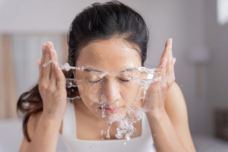 An asian woman washing her face