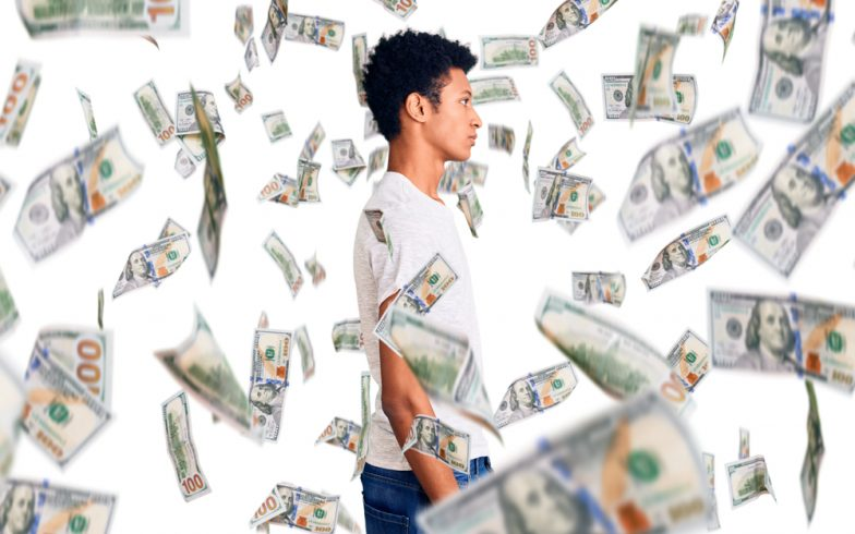 A young man standing with money all around him