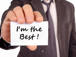 Man holding a card with I'm the best written on it