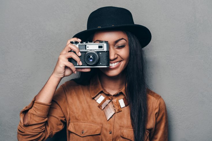 Woman smiling while holding a camera