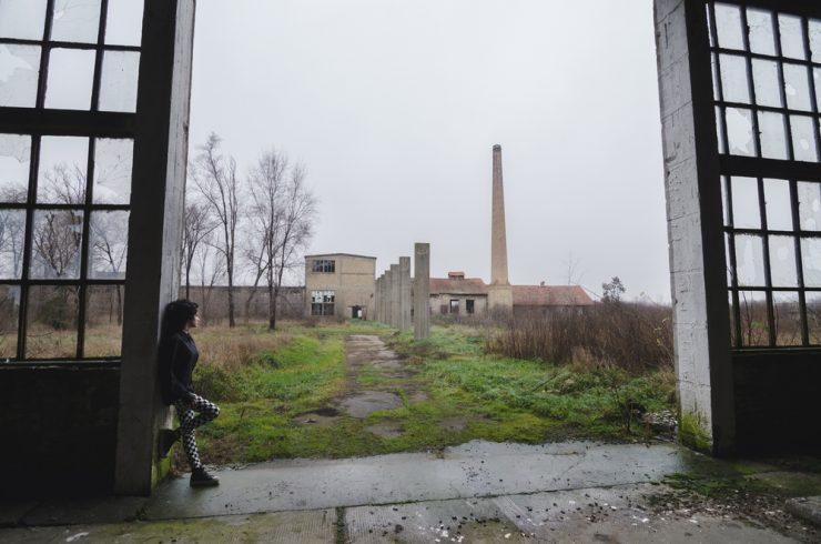 Young girl standing in an abandoned factory