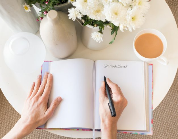 A top view of a woman's hands writing in a journal