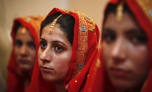 Brides-to-be wait during a mass wedding ceremony in Karachi March 25, 2012. A total of 51 couples from the rural coastal area of Karachi took wedding vows during a mass ceremony, funded by non-government organizations. REUTERS/Akhtar Soomro (PAKISTAN - Tags: SOCIETY)