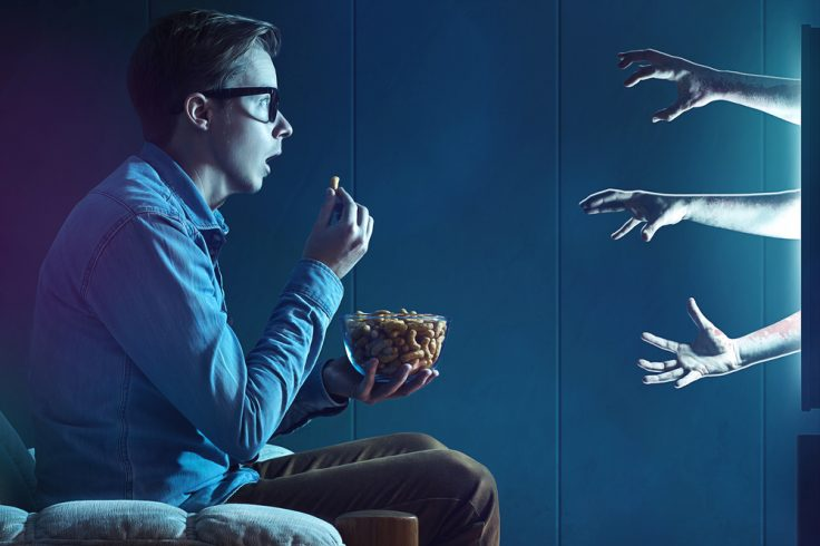 Yoing boy eating popcorns while watching a horror movie