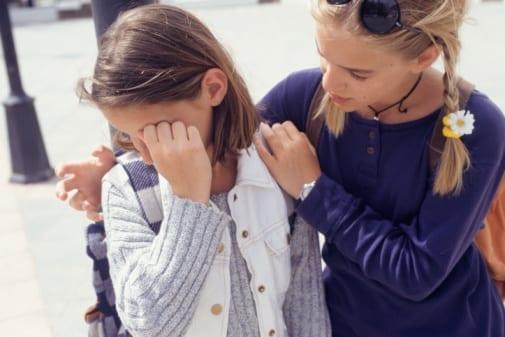 Young girl (10-11) crying, teenage girl (14-15) comforting her pain