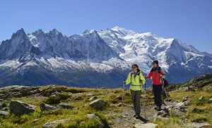 Woman and man hiking with view to Aiguilles du Chamonix, Aiguille du Midi and Mont Blanc, Montblanc range, Chamonix, Savoy, France trek