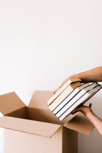 crop-person-packing-stack-of-books-in-carton-box-4498137