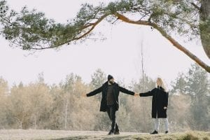 full-body-of-cheerful-couple-strolling-together-near-tree-in-4127588