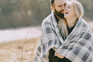 happy-couple-hugging-under-plaid-in-nature-4127557