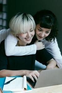 happy-women-using-laptop-in-workspace-4126748