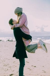 man lifting woman up and hugging her