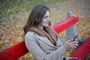 woman-in-beige-coat-holding-smartphone-sitting-on-bench-712433