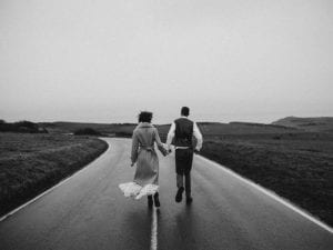 grayscale-photo-of-couple-walking-on-road-3617517