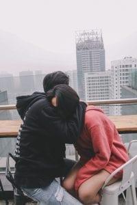 man-hugging-woman-sitting-on-chair-786924