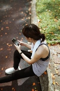 woman-using-smartphone-while-sitting-on-sidewalk-in-park-4428990