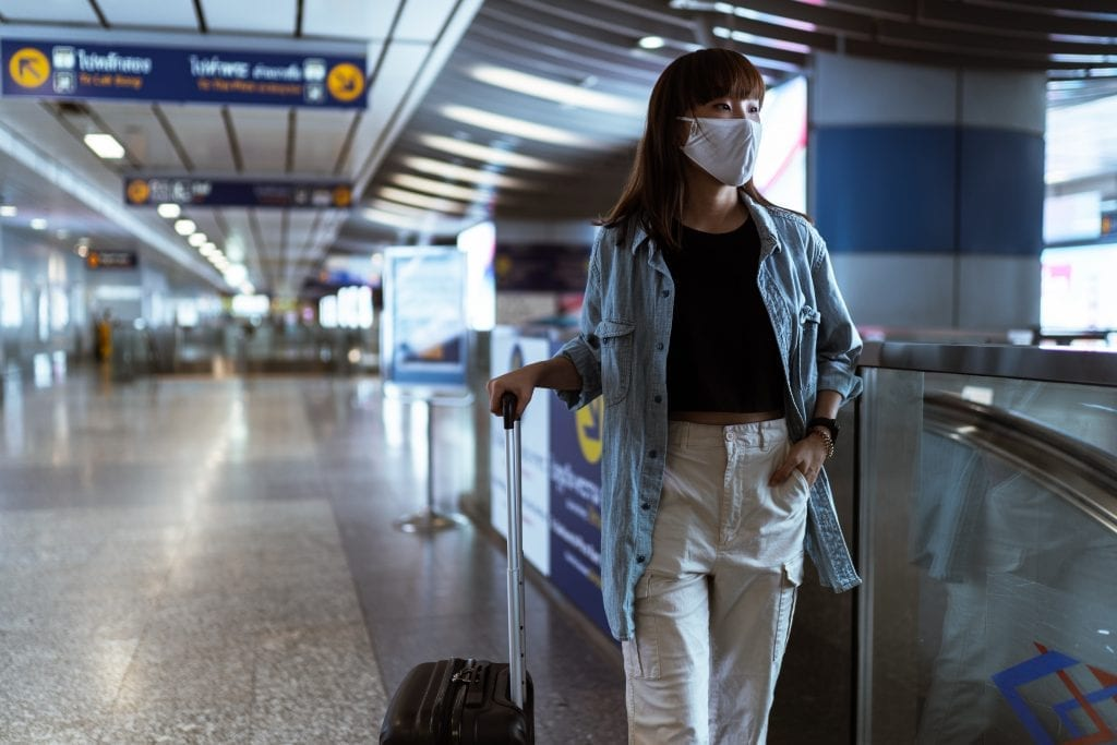woman-with-a-face-mask-holding-her-luggage-4436363