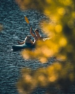 A boy kayaking in the river with his dog