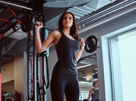 Beautiful brunette female in sportswear holds a barbell while training in a fitness club or gym.